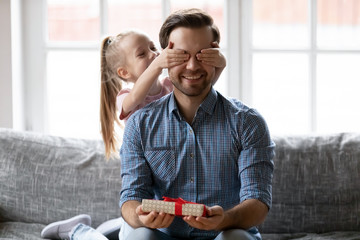 Excited little daughter greeting young dad with birthday