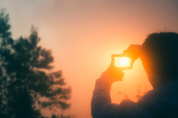 Young man making frame round the sun with his hands in sunrise,Future planning idea concept , copy space,warm retro tone.
