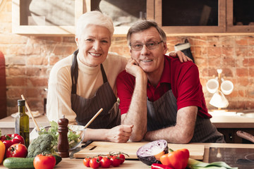 Cheerful senior couple posing at kitchen interior