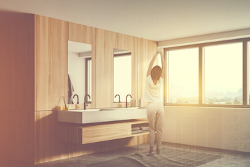 Woman in white and wooden bathroom with sink