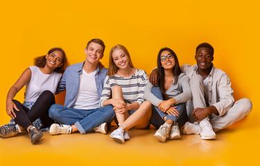 Joyful students having fun over yellow studio background Papier Peint