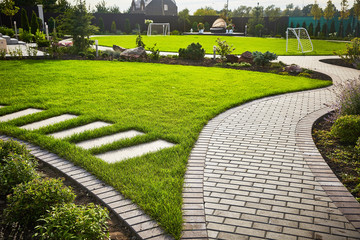 Photo sur cadre textile Gris traffic Landscaping of the garden. path curving through Lawn with green grass and walkway tiles.