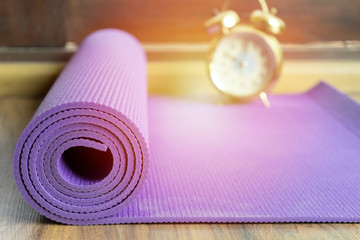 In de dag Ontspanning close up of yoga mat and alarm clock on the table, sport and healthy concept