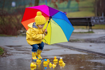 Beautiful funny blonde toddler boy with rubber ducks and colorful umbrella, jumping in puddles and playing in the rain Fotobehang