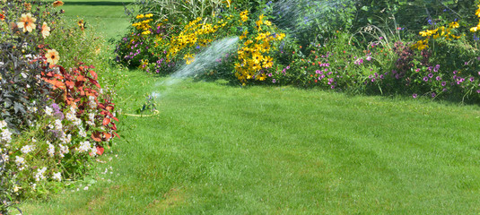 Foto op Canvas Tuin sprinkler in the lawn watering flowers in a beautiful garden in summer