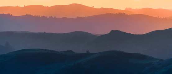 Sunset view of hills and valleys, each layer colored differently;  Santa Cruz mountains ; San Francisco bay area, California