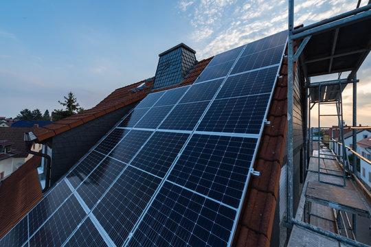 Solar-Panels auf Hausdach mit Gerüst am linken Rand