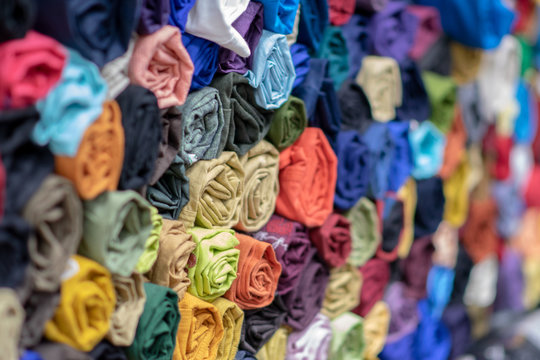 Rolls of vibrant colorful tshirts stacked in a store, comfortable seasonal clothing