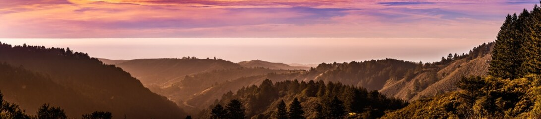 Panoramic sunset view of hills and valleys in Santa Cruz mountains; clouds covering the sky and the...