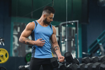 Wall Mural - Handsome athlete training biceps with dumbbells at gym