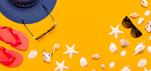 Wall Mural - Summer beach sea accessories. Coral flip flops, blue straw hat, sunglasses, shells, starfish on yellow background top view flat lay copy space. Summer background. Holiday vacation travel concept