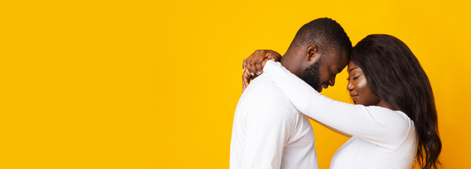 Happily married black couple hugging over yellow background