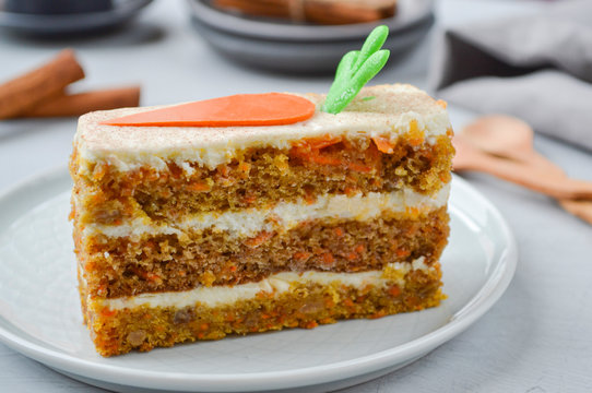 National Carrot Cake Day.  Carrot cake with cream cheese frosting decorated with chocolate carrots on a light wooden background. Close-up, top view