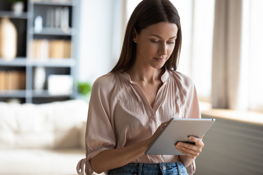 Young woman busy browsing web on modern tablet gadget