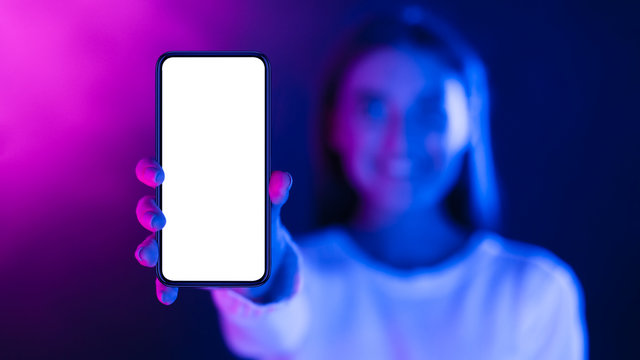 Woman showing phone with blank screen in neon lights