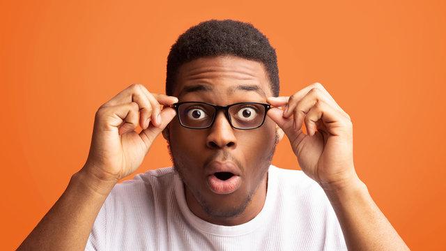 Surprised african american guy touching his eyewear