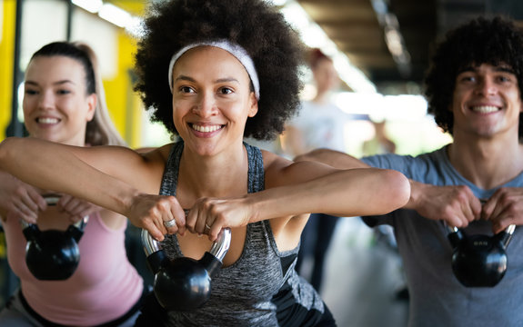 Group of happy multiracial friends exercising together in gym