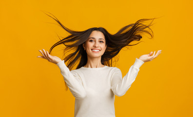 Portrait of beautiful brunette girl with flying hair over yellow background