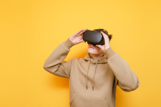 Young guy in light hoodie and VR helmet stands on a yellow background and look away at the copy space with a serious face.Young man in virtual reality helmet isolated on yellow wearing casual clothes
