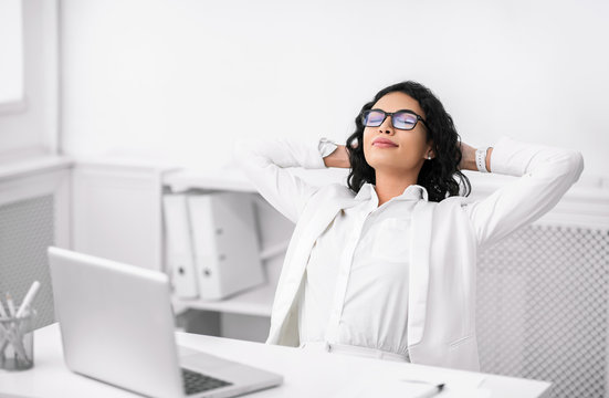 Hispanic businesswoman in glasses relaxing at work