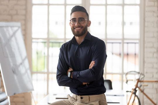 Portrait of smiling Arabian male boss posing in office