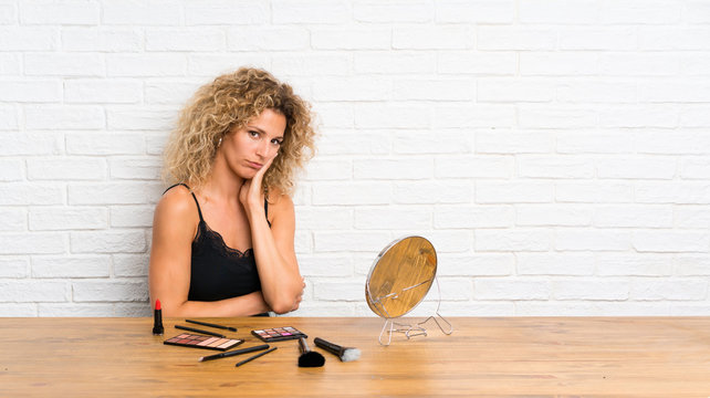 Young woman with lots of makeup brush in a table unhappy and frustrated