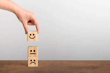 Hand picked up the happy face smile symbol on wooden cube