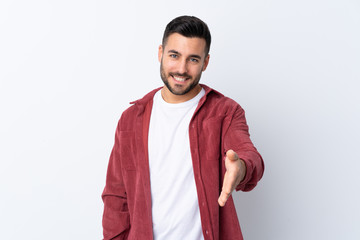 Young handsome man with beard wearing a corduroy jacket over isolated white background shaking...