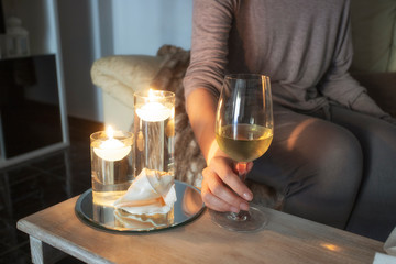 Woman  sitting in sofa and holding glass winein living room. Relax at cosy home concept.