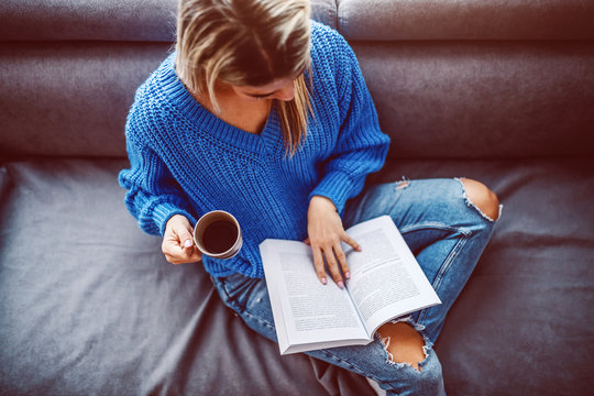 Top view of blond caucasian young woman in sweater sitting on sofa in living room, drinking coffee and reading book.