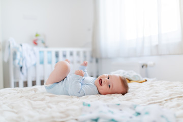 Side view of adorable chubby six months old baby boy lying on bed, smiling and looking at camera. Bedroom interior. Happy childhood concept.