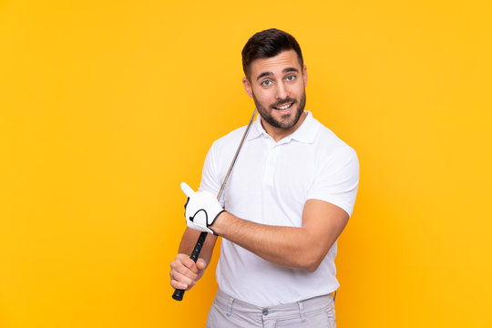 Man over isolated yellow background playing golf and pointing to the lateral