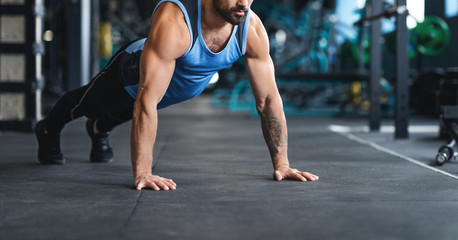 Wall Mural - Sportsman making plank or push ups exercise at gym