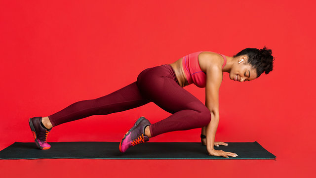 Fitness girl working out on yoga mat over red background