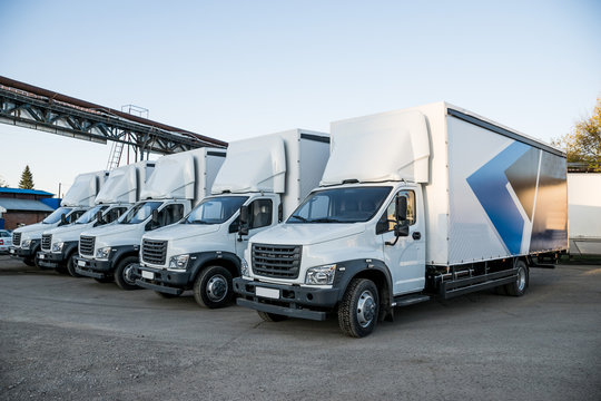Five white truckers in the parking lot are waiting for the next delivery of goods. The concept of a transport company for the delivery of goods worldwide.
