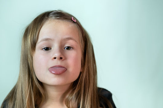 Close-up portrait of little girl with long hair sticking out her tongue.