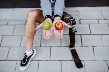 Fotomurales - Top view of Caucasian man with artificial leg sitting on ground and holding red and green apples in each hand.