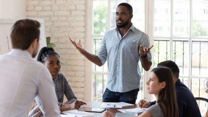 Angry diverse colleagues dispute at company office meeting