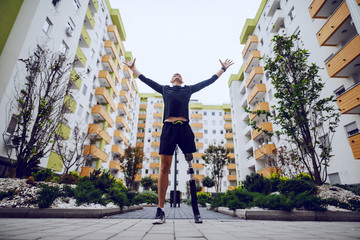Fotomurales - Low angle view of handsome sportsman with artificial leg standing with hands in the air outdoors surrounded by buildings.