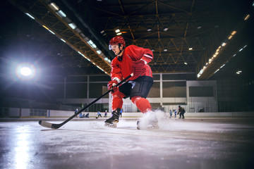 Dedicated strong caucasian handsome hokey player playing hockey on ice in hall.