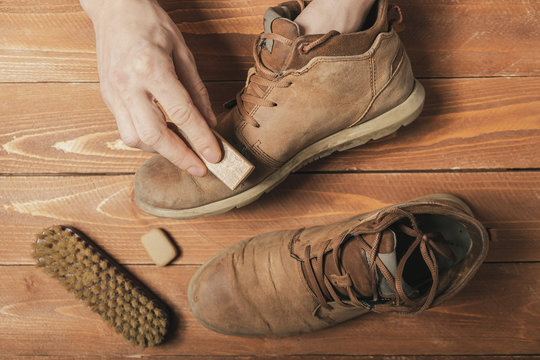 A man cleans his nubuck boots with a small brush
