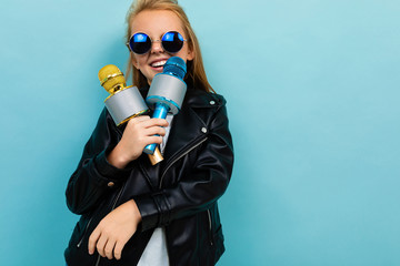 Photo sur Aluminium Magasin de musique Caucasian teenager girl with brown hair in black jacket, blue sunglasses sings songs with blue and yellow microphones isolated on blue background