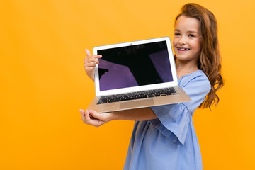 picture of a cute child in a dress holding a laptop with a breadboard in his hands on a bright yellow background