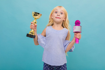 Portrait of little caucasian girl in blue t-shirt with long blonde hair holds a gold cup and microphone isolated on blue background
