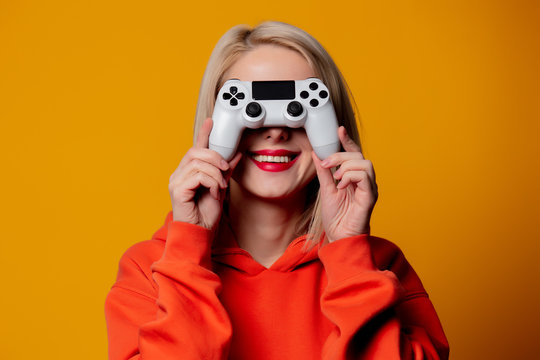 gamer girl with white gamepad on yellow background