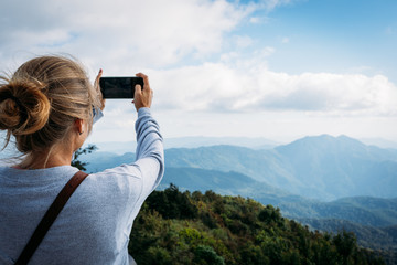Blonde girl taking pictures with the mobile of the horizon views in the mountains