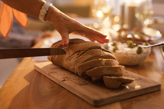 Close-up of woman cutting bread.