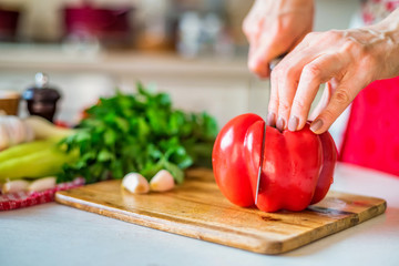 Female hand with knife cuts bell pepper in kitchen. Cooking vegetables