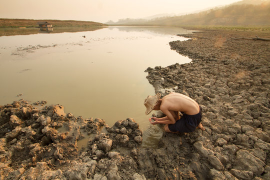 Man taking water from drying pond, river on summer metaphor water crisis and climate change impact.
