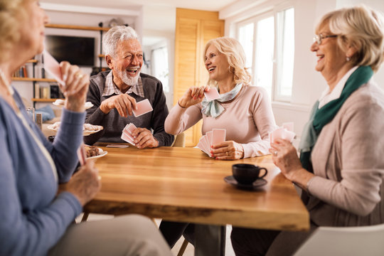 Cheerful senior friends having fun while playing cards together.
